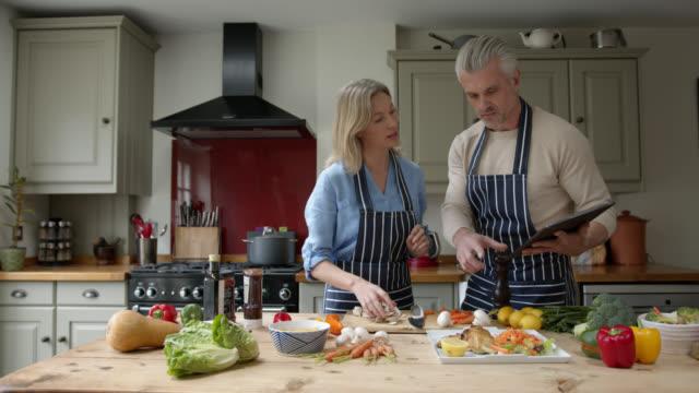 vídeos de stock, filmes e b-roll de casal feliz cozinhando em casa seguindo um tutorial em um tablet digital - receita