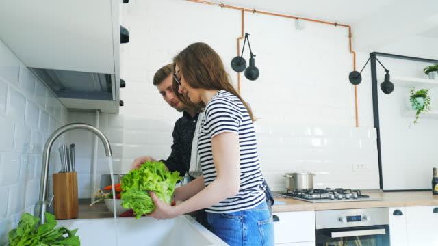 vidéos et rushes de heureux couple cuisine ensemble. - préparation