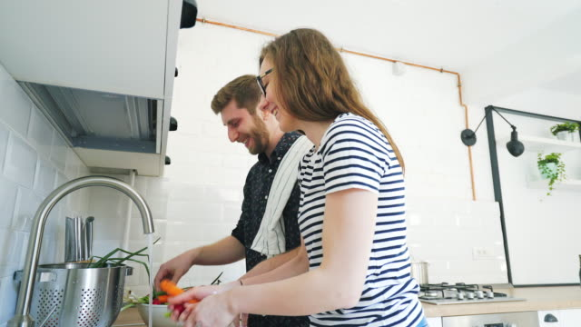 happy couple cooking together. - wife stock videos & royalty-free footage