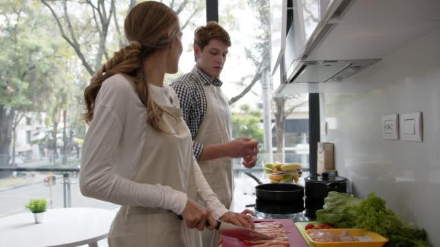 vídeos de stock, filmes e b-roll de casal feliz cozinhando juntos enquanto conversavam e sorriam - almoço