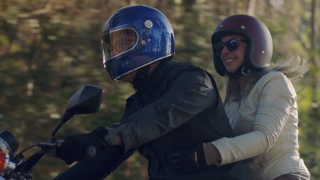 SLO MO. Happy couple cruise down forest road on motorcycle.