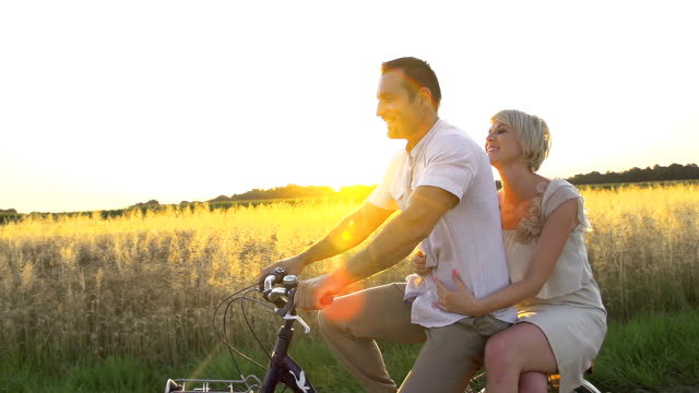 HD SUPER SLOW MO: Happy Couple Cycling In Countryside