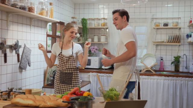 vídeos de stock e filmes b-roll de happy couple dancing together in the kitchen - casal casado