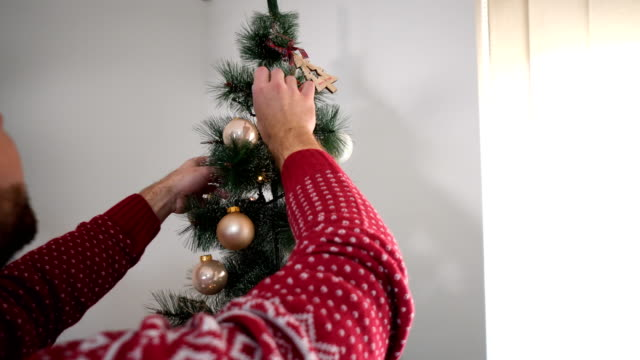 glückliches paar dekorieren weihnachtsbaum in ihrem haus. lächeln mann und frau gemeinsam feiern weihnachten oder silvester. weihnachtsbaum decoration.family - weihnachtsbaum stock-videos und b-roll-filmmaterial