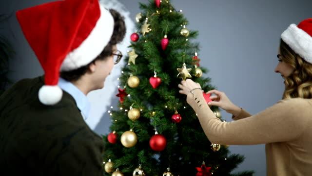 happy couple decorating christmas tree - santa hat stock videos & royalty-free footage
