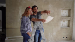 Happy couple doing a home renovation looking at a design on paper while pointing at a wall and talking