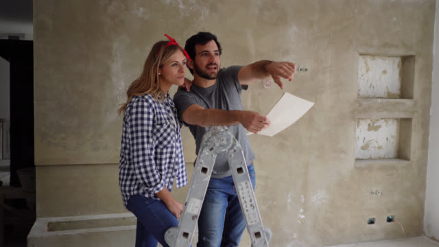 happy couple doing a home renovation looking at a design on paper while pointing at a wall and talking - realizzazione video stock e b–roll