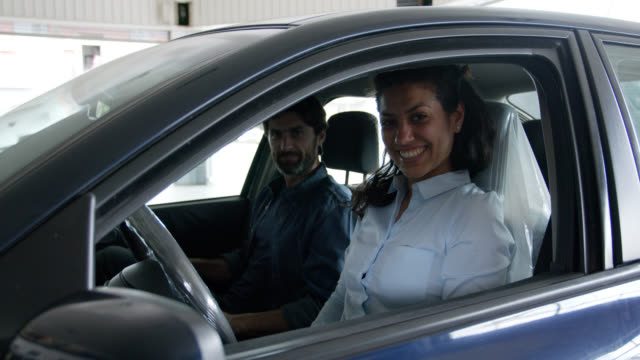 happy couple doing a test drive at the car dealership smiling at camera - test drive stock videos & royalty-free footage