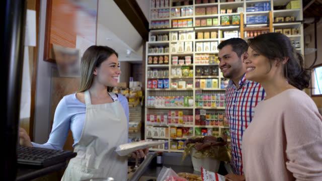 vidéos et rushes de heureux couple faisant caisse au supermarché et sympathique vendeuse parlant pour eux - caisse