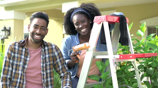 happy couple doing some home repairs outside house - caulk gun stock videos and b-roll footage