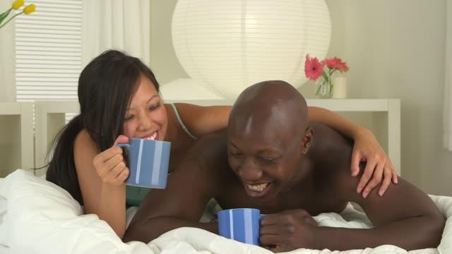 vídeos de stock, filmes e b-roll de happy couple drinking coffee in bed - molécula de cafeína