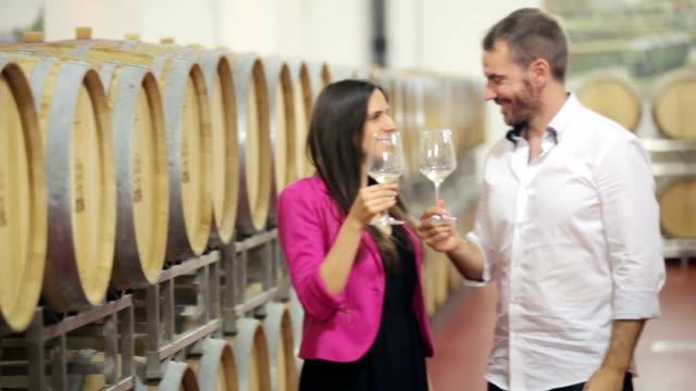 Happy couple drinking white wine in vine cellar