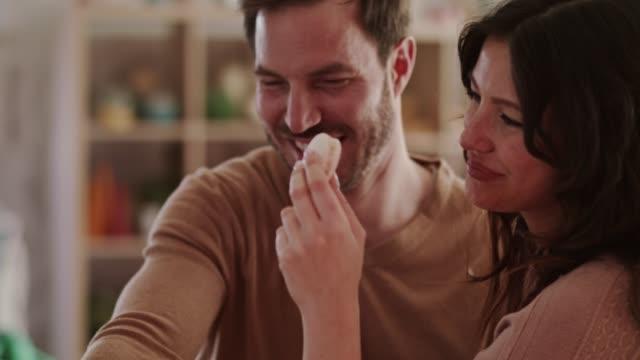 vidéos et rushes de couples heureux mangeant des sucreries et ayant le thé ensemble - trentenaire