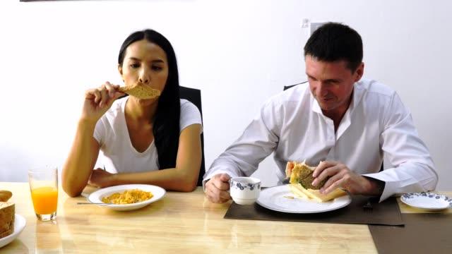vídeos y material grabado en eventos de stock de pareja feliz comer comida en la mesa de la cocina juntos - happy meal
