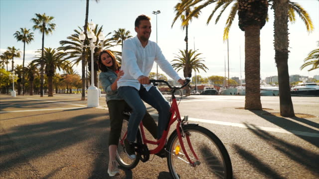 happy couple enjoying a bicycle ride together. - life balance stock videos & royalty-free footage