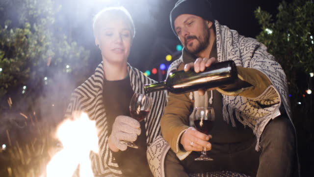 A Happy Couple Enjoying A Bonfire At Night Drinking Wine
