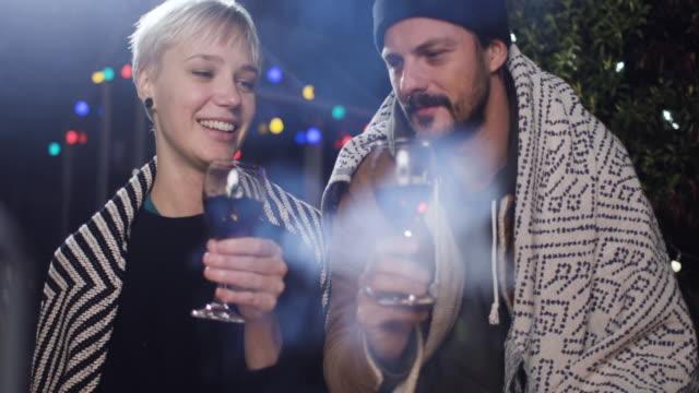 vídeos de stock e filmes b-roll de a happy couple enjoying a bonfire at night drinking wine - 30 39 years