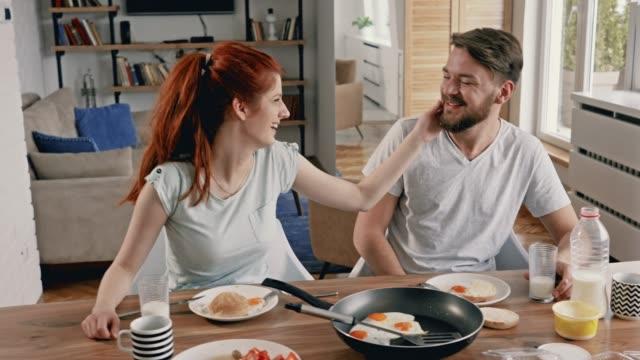 vídeos de stock, filmes e b-roll de casal feliz desfrutando na hora do almoço e comunicando-se pela manhã. - copo