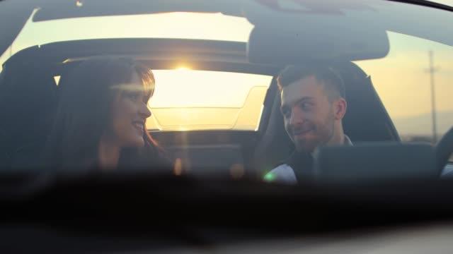 glückliches paar flirtet, redet und lächelt im cabrio - flirten stock-videos und b-roll-filmmaterial