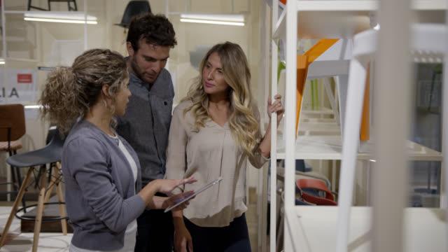 glückliches paar folgt verkäuferin in einem möbelhaus zeigt ihnen produkte, während sie ein tablet hält, um auf die preise zu schauen - designer einrichtung stock-videos und b-roll-filmmaterial