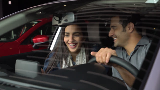 vídeos de stock e filmes b-roll de happy couple going out for a test drive of a car they want to buy - stand de carros