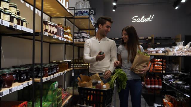 vidéos et rushes de l'heureux couple faire l'épicerie au marché et en regardant une liste sur un smartphone - aliments et boissons