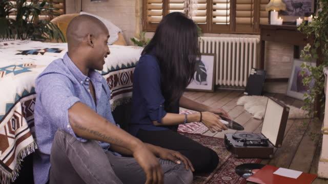 vídeos de stock, filmes e b-roll de happy couple hanging out playing records at home - casal jovem