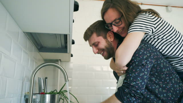happy couple having fun in the kitchen. - washing up stock videos and b-roll footage