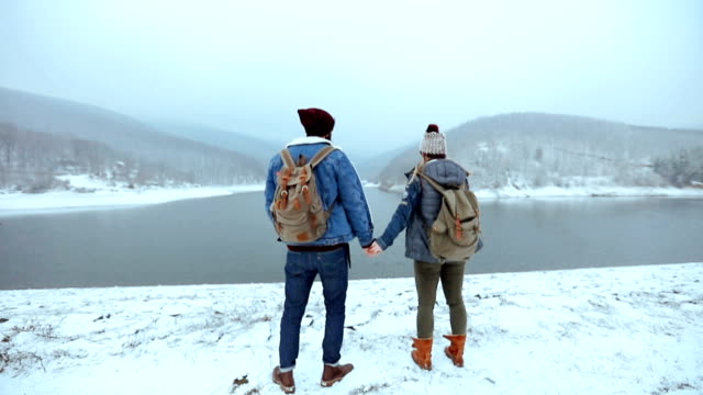 Happy couple holding hands and kissing outdoors, winter wonderland
