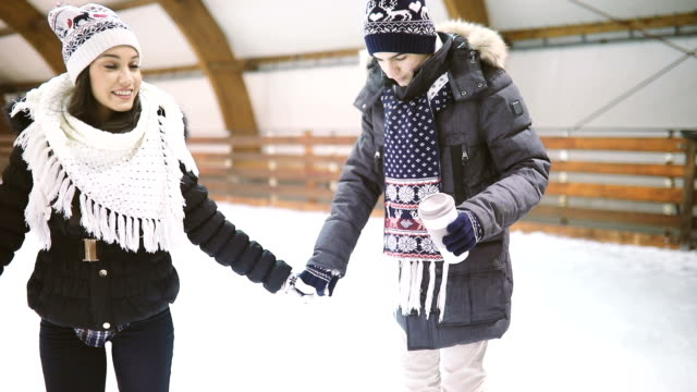 happy couple holding hands on skating rink - ice rink stock videos & royalty-free footage