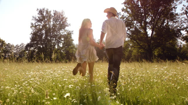 SLO MO DS Happy couple holdings hands running across meadow