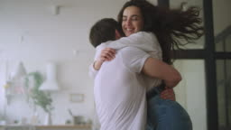 Happy couple hugging at new home. Love couple spinning around