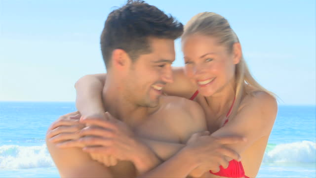 happy couple hugging on a beach / cape town, western cape, south africa - 談笑する点の映像素材/bロール
