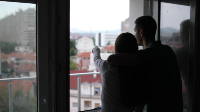 vídeos de stock e filmes b-roll de happy couple hugging while looking trough the window of their new flat - terraço