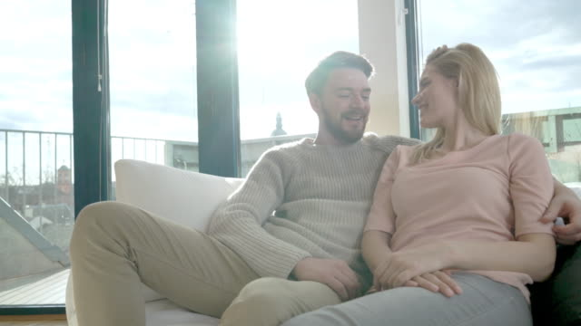 happy couple in love communicating while relaxing on the sofa at home. - heterosexual couple stock videos & royalty-free footage