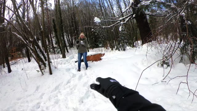 Happy couple in love in slow motion footage making snow fight in winter landscape in the Montseny nature reserve during weekend trip in the nature.