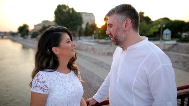 Happy couple laughing on the bridge
