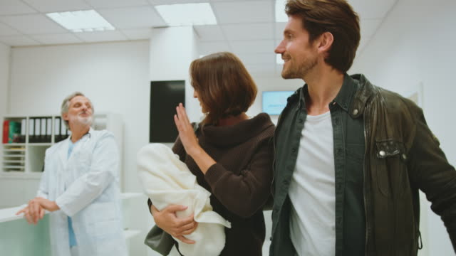 happy couple leaving hospital with newborn baby - leaving hospital stock videos & royalty-free footage