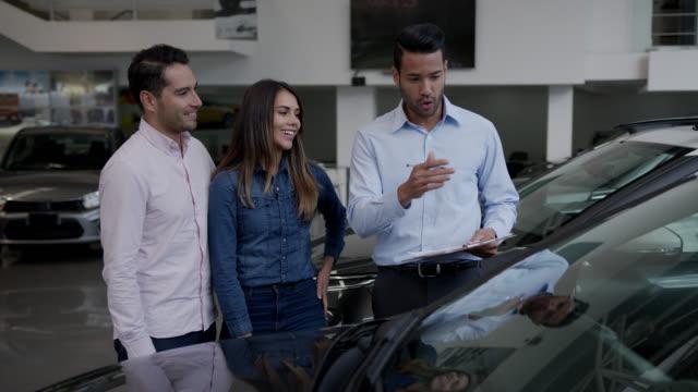 vídeos de stock, filmes e b-roll de casal feliz ouvindo vendedor amigável explicar algo sobre o carro, enquanto ambos parecem muito animado - sale