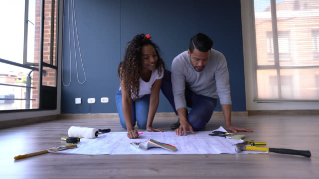 happy couple looking at a blueprint and planning how to decorate their new home very excited - tape measure stock videos & royalty-free footage