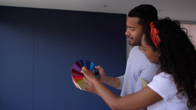 happy couple looking at a color swatch and the wall they want to paint at their new home - color swatch stock videos & royalty-free footage