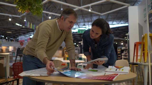 vídeos y material grabado en eventos de stock de feliz pareja mirando un diseño en una tableta y un boceto, trabajando en un proyecto de renovación del hogar en una tienda de muebles - diy