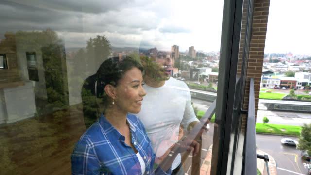 vídeos de stock, filmes e b-roll de casal feliz olhando pela janela de sua casa nova - apartamento