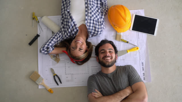 happy couple lying down on floor on top of a blueprint and tools ready for a diy project smiling at camera - rebuilding stock videos & royalty-free footage