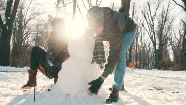 happy couple making a snowman. - making a snowman stock videos & royalty-free footage