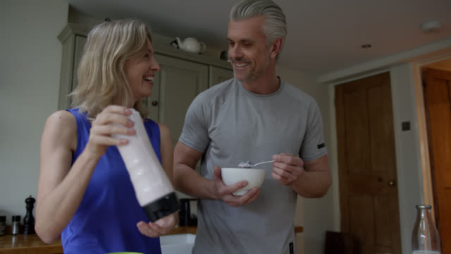 happy couple making post workout smoothie at home using a blender - dessert stock videos & royalty-free footage