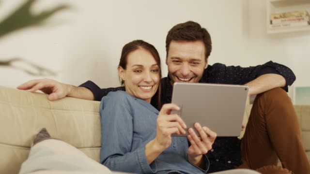 Happy couple making video call on digital tablet