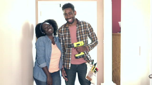 Happy couple, man with drill and tool belt