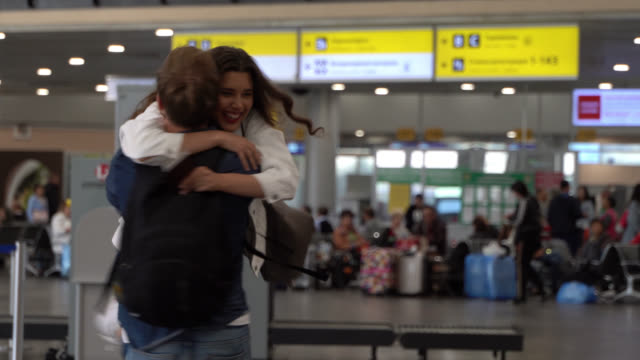 vídeos de stock e filmes b-roll de happy couple meeting at the airport hugging very excited ready to travel - aeroporto