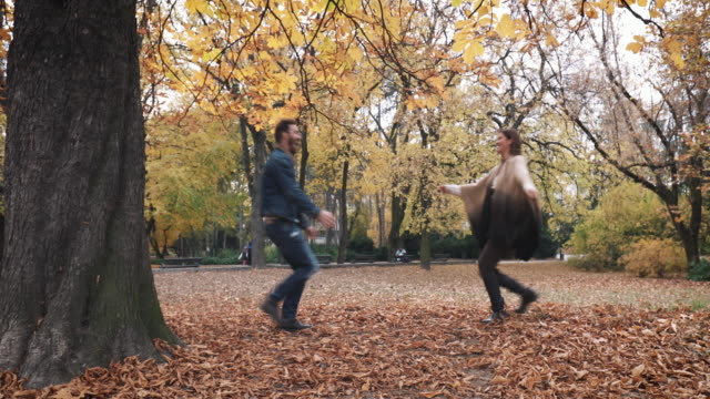 Happy couple meeting in autumn park and spinning out of joy.